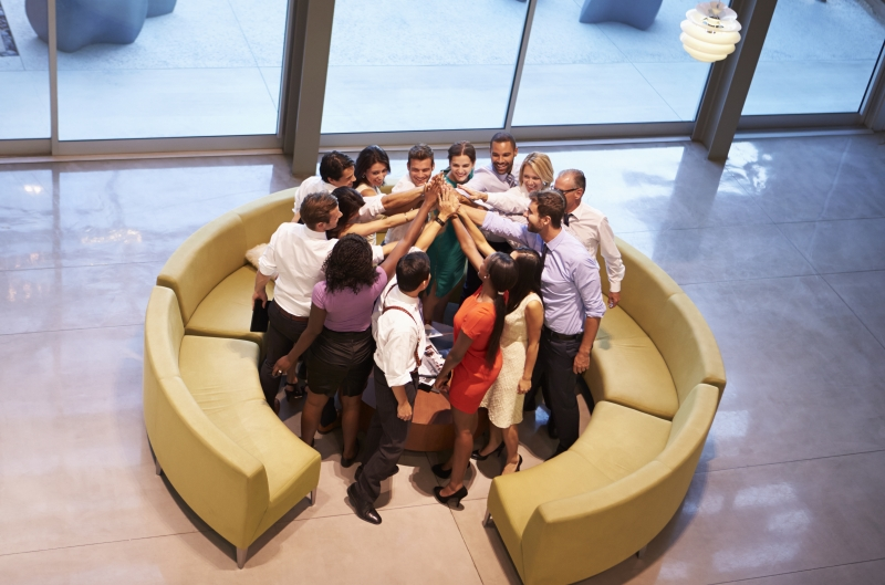 11827955-businesspeople-giving-each-other-high-five-in-office-lobby